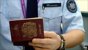 A passport being checked by a UK Border Agency staff member.