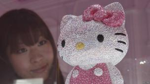 A woman looks at a crystal studded Hello Kitty in Tokyo