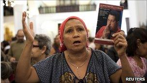 A woman attends Mass to pray for Hugo Chavez to make a speedy recovery