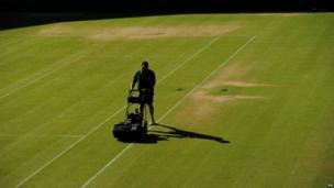 A man mows the grass on a court