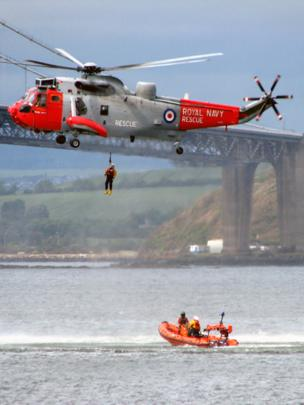 Search and rescue helicopter winching a man to safety with a lifeboat in the water below