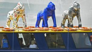 Three colourful, life-size gorilla sculptures on top of a boat in Bristol.