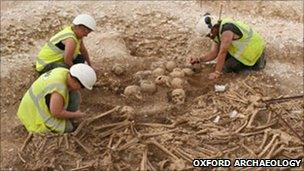Archaeologists working at burial pit