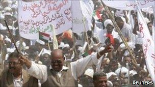 Sudan's President Omar al-Bashir gestures to supporters during a visit to Diwayaem town in White Nile State in Khartoum, 7 July 2011
