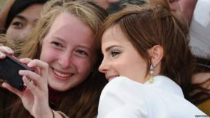 Emma Watson poses with a fan