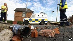 Workers sweep debris and rubbish from a street as a large clean up operation gets underway in Ardoyne