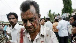 An injured man walks away from Mahim railway station following explosions on the rail network in Mumbai, India, 11th July 2006