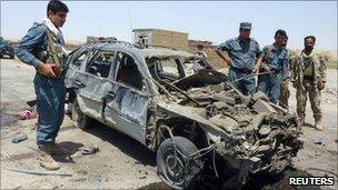 Security forces by a bomb-damaged car in Kunduz, Afghanistan (19 June 2011)