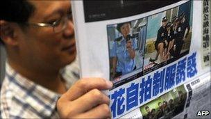 A man reads a local newspaper in Hong Kong on July 14, 2011 featuring front page photos of police woman posing in controversial images.
