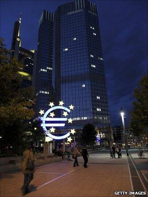 A Euro logo stands in front of the headquarters of the European Central Bank