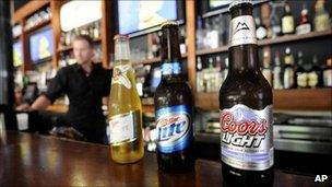 Three bottles of MillerCoors beer sitting on a bar