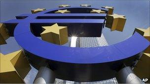 In this August 6, 2009 file photo, the sun is reflected on the facade of the European Central Bank ECB Tower, seen through the Euro symbol, in Frankfurt, central Germany.