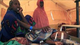 A Somali woman comforts her son as he rests in a hospital