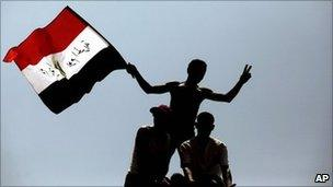 Protesters wave the Egyptian national flag as they perch on top of a street lamp in Tahrir Square in Cairo, Egypt, Friday, 15 July 2011