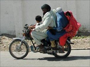 A family rides on a motorcycle in Lashkar Gah