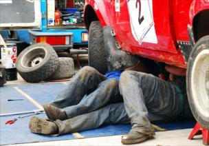 Mechanics work on a car