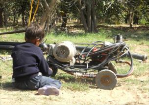 A boy playing with a discarded engine.