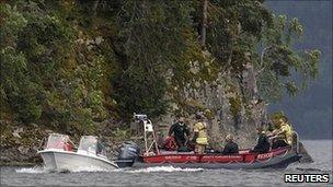 Rescue boats patrol near the shore of the small, wooded island of Utoeya