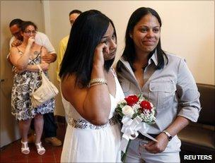 Same-sex couple Mishan Moore (L), 39, wipes a tear as her partner Jacqueline Rodriguez, 34, looks on during their wedding ceremony at Queens Borough Hall in New York, 24 July