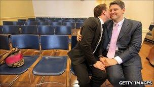 A gay couple embrace on their wedding day at the Brooklyn City Clerk's office in New York, 24 July