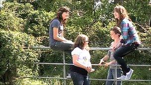 Girls siting on a gate