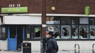 A policewoman by a row of smashed windows in Tottenham, north London