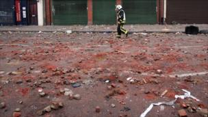A fireman walks down a street covered with debris after the riots.