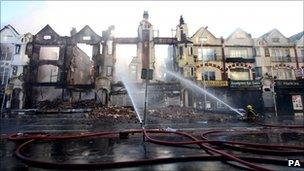 Fire crews douse burnt out buildings on London Road in Croydon, Surrey