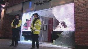 Two police officers guarding a shop