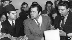 Orson Welles, centre, speaks to reporters in October 1938