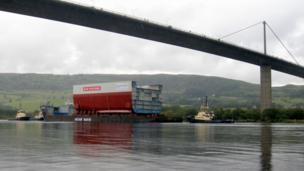 The hull of a new Royal Navy aircraft carrier on a barge under the Erskine bridge