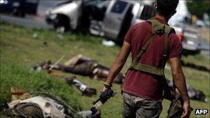 A rebel soldier walks past dead pro-Gaddafi soldiers in Tripoli, Libya (25 Aug 2011)