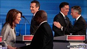 Republican presidential hopefuls shake hands at a debate in Iowa