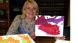 Kathy O'Neill from Paignton Zoo with some of N'Dowe the lowland gorilla's paintings.