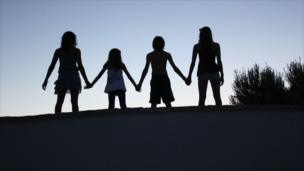 The silhouettes of four children holding hands in a line