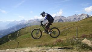 A man jumps over a mound of earth on a mountain bike
