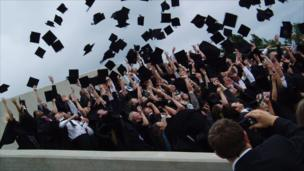 A group of graduating students throw their mortar boards in the air