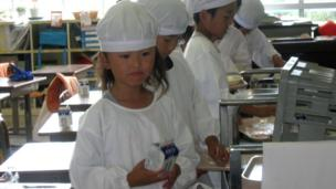 Young children returning their lunch trays Onagawa in Japan.