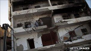 People stand on a damaged balcony of a war torn building on Tripoli Street, on September 03, 2011 in Misrata