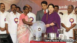 J Jayalalitha giving away freebies that she promised during her campaign