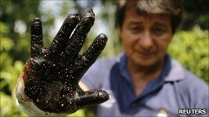 Environmentalist Donald Moncayo shows a glove covered in oil after testing an area in Lago Agrio, January 2011