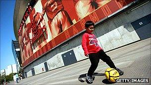 A youngster plays football outside Arsenal's Emirates Stadium