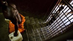 A prisoner carries a carton of water in Liberia's Monrovia Central Prison - 2011