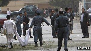Afghan policemen carry the body of a suicide attacker in Kabul (13 Sept 2011)