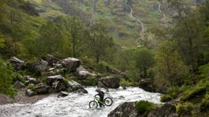 Biker crossing water in Glencoe