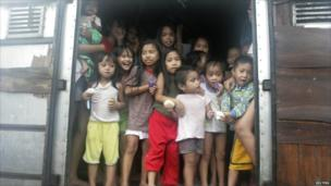 Children look out from the back of a delivery truck