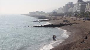 People in the water and on the beach at Eastbourne in south England