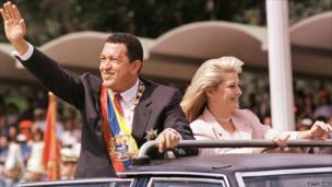 Venezuelan President Hugo Chavez Frias, accompanied by his wife Marisabel Rodriguez de Chavez, waves to supporters as he arrives to preside over a parade in his honour.