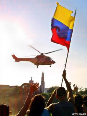 Supporters of Venezuelan President Hugo Chavez wave a national flag as his helicopter leaves the Miraflores presidential palace in Caracas 14 April 2002.