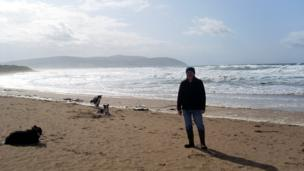 Martin and three Border collies on the beach